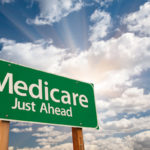 Medicare just ahead road sign over sky background