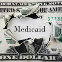 A dollar with medicaid word inside