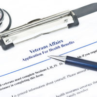 Veteran Affairs Health Benefits Application with pen and stethoscope on side