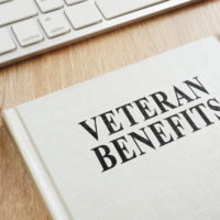 Handbook about Veteran Benefits on a desk surrounded by office supplies