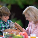 younger boy and older woman pet cute kitten