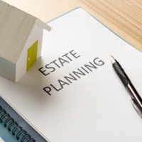 mini wooden house on top estate planning documents