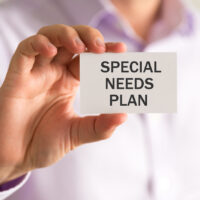Businessman holding a card with SPECIAL NEEDS PLAN message