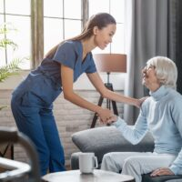 Happy female professional caregiver taking care of elderly woman at home