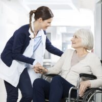 Physiotherapist Consoling Senior Woman Sitting In Wheelchair